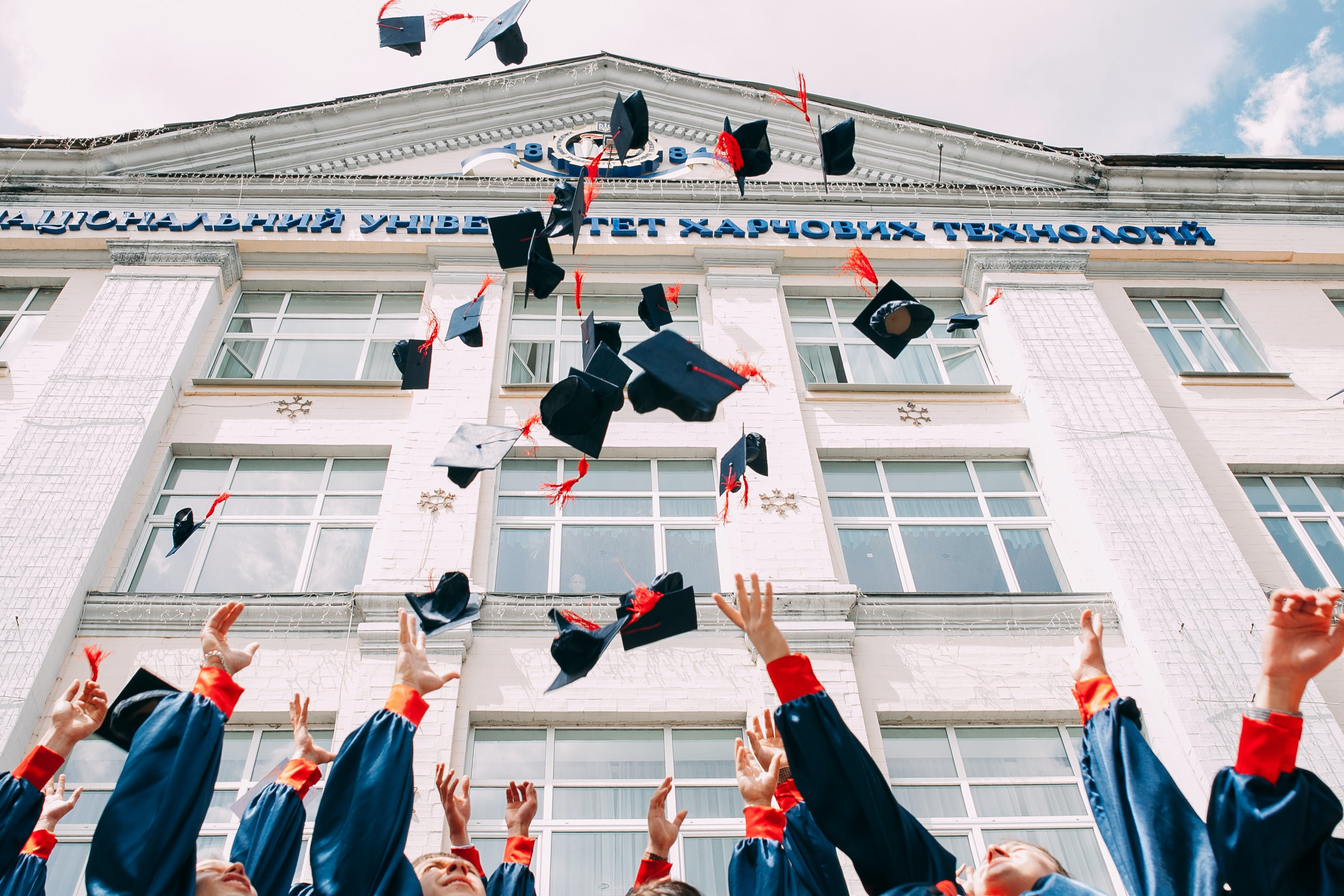 students throwing academic caps into the air
